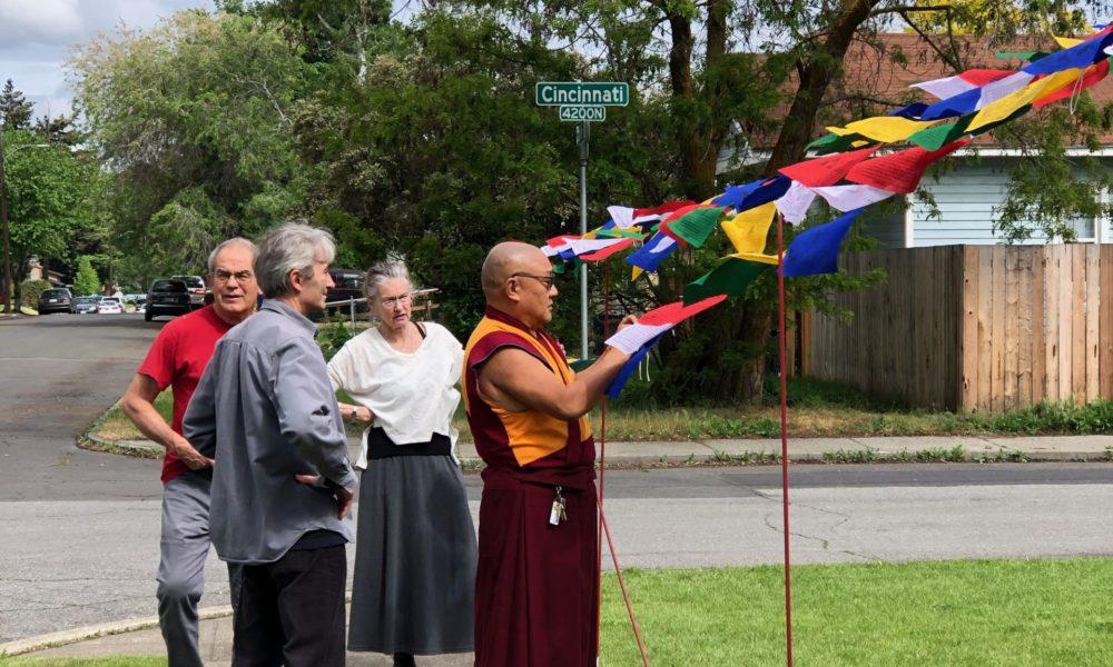 Venerable Geshe Phelgye hanging prayer flags at the Buddhist Institute